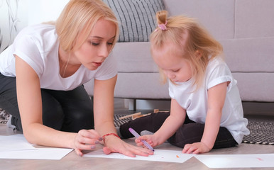 Little charming blond girl refuses to paint felt-pen with her attractive mom sitting near the sofa.