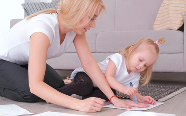 Little charming blond girl painting blue felt-pen with her mom sitting near the sofa.