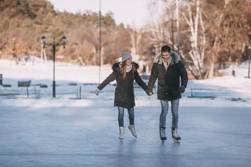 Full length of happy couple holding hands while enjoying ice-skating on rink