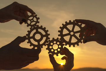 the hands of people are holding gears against the background of the evening sky. business team work.