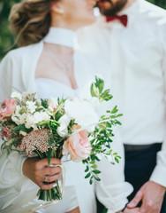 stylish bearded groom and beautiful bride posing outdoors