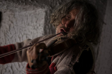 Old man with tousled long hair singing as he plays a violin