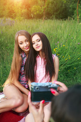 attractive pretty young woman talking pictures her friends outdoors in summer
