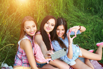 Happy three friends women a selfie on a summers day in park