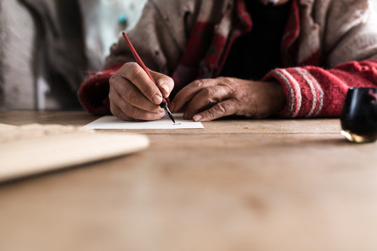 Old man with dirty hands writing a letter using a nib pen and ink