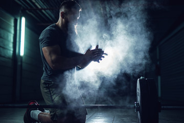 Close up view of focussed hardworking active fitness strong muscular bearded bodybuilder. Wall mural