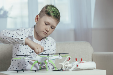 Confident boy adjusting drone on coffee table while sitting at home