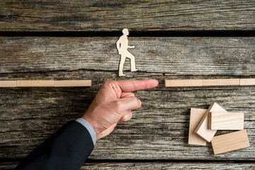 Businessman supporting paper cut out of a man walking forwards to success