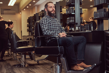 Hipster bearded male in a flannel shirt and jeans sitting on a barber chair after shearing in a hairdressing salon.