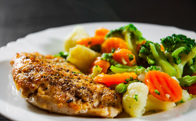 chicken fillet with Mixed vegetables. cauliflower, broccoli and carrots in white plate on a wooden background.