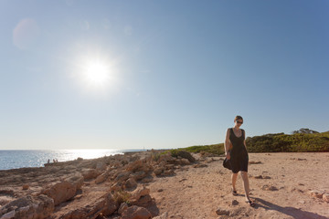 Cap de Ses Salines, Mallorca - A young woman going out for a walk at the beach of Ses Salines
