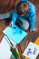 Little boy drawing a colorful picture of a car using pencil crayons