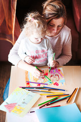 Mom with little daughter drawing a colorful pictures using pencil crayons