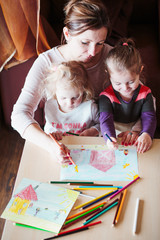 Mom with little girls drawing a colorful pictures using pencil crayons