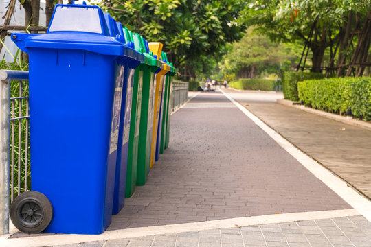 Row of Wheelie Bins. Many trash carts set in the park. There are blue, green and yellow tanks. Copy space.