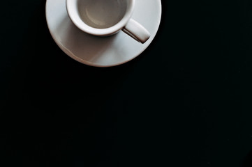 white coffee mug on black background top view