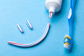 Tooth-paste in the form of a face with a smile. Tube of toothpaste and toothbrush on a blue background. Refreshing and whitening toothpaste.