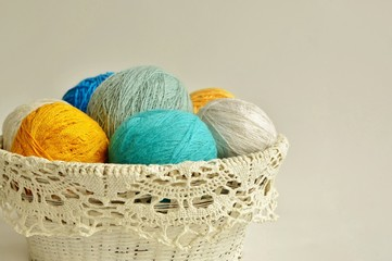 Balls of multicolored yarn in basket on white background.