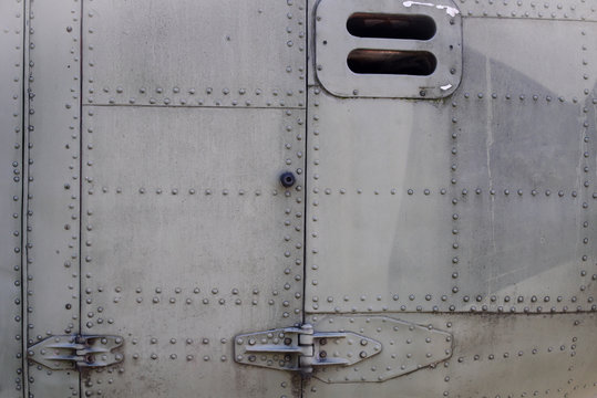 Old silver metal surface of the aircraft fuselage with rivets. Fuselage detail view. Airplane metallic fuselage detail with rivets.