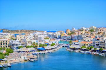 Fotobehang Kust Agios Nikolaos, Crete Island / Greece. Panoramic view of the famous coastal town of Agios Nikoloaos in Lasithi prefecture of Crete. Amphitheatrically built town around Voulismeni lake. Sunny day