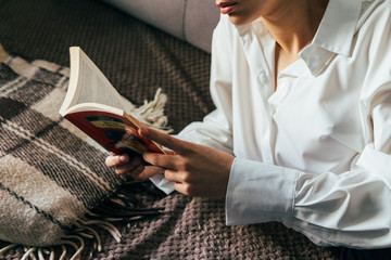 girl reading a book in a warm blanket. woman lies, lay down on the bed, a blanket, a sofa, a couch and holds a book. Girl reading a book