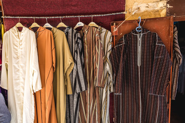 Djellaba brown and Dark cloths hanging in shop- Morocco.