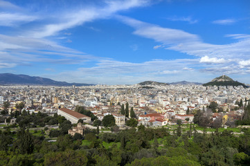 Athens, Attica - Greece. Panoramic view of the city of Athens as seen from the vantage point of Areopagus hill in Plaka, Acropolis. Lucabettus hill in the background. Sunny day with blue cloudy sky
