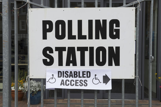 British election polling station sign with disabled access hanging on fence in London, UK