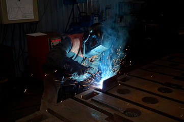 Welder at work when processing metal in production. Sparks in the welding of steel.
