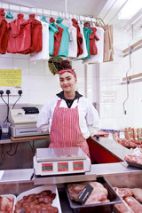 Portrait of woman behind counter in butcher's shop