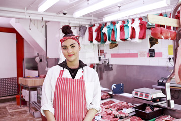 Portrait of woman wearing apron in butcher's shop