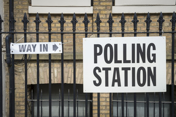 British election polling station sign with way in arrow hanging on fence in London, UK