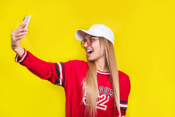 Portrait of a young attractive woman in sunglasses making selfie photo on smartphone isolated on a yellow background