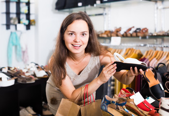 Young woman choosing shoes in store .