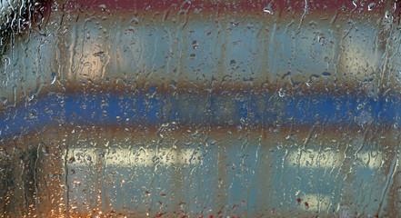 Facade seen through a window with raindrops