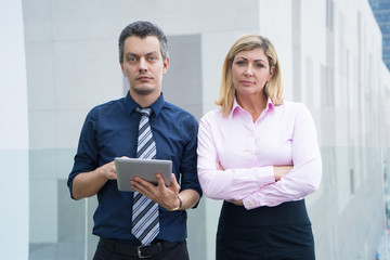 Serious confident business people working together. Successful lady and her assistant with tablet looking at camera and standing outdoors. Strong business team concept