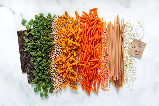 different types of gluten-free paste from chickpeas, red lentils, algae and healthy cereals on a white marble table. labels for writing text. shot from above. food background