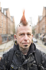 Portrait of tattooed man wearing ear plugs