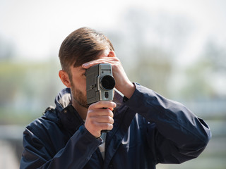 bearded man professional cameraman observes and shoots an 8mm movie camera