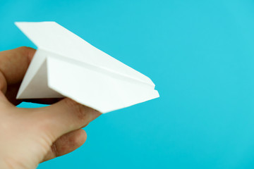 Hand holding paper airplane on light blue background.