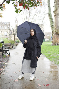 Portrait of a young Muslim woman with an umbrella