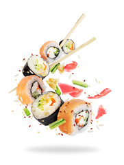 Different fresh sushi rolls with chopsticks frozen in the air on white background