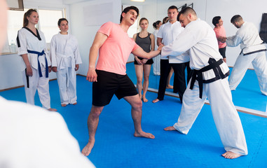 Coach explaining painful hold in taekwondo class