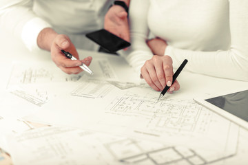 Employees work on blueprints or engineering plans in the office. Engineering.