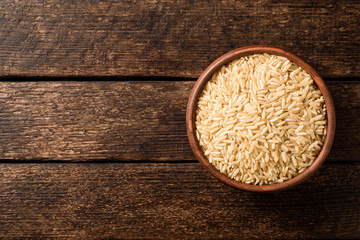 Raw brown rice in ceramic bowl on dark rustic wooden background