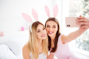 Portrait of girlish, stylish, pretty, attractive, charming, cheerful, cute, successful girls wearing rabbit ears shooting selfie on front camera, using smart phone, spending time together indoor, room