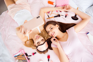 Portrait of joyful, cheerful, best,  pretty, charming, stylish, successful girls in pink, white outfit using smart phone, holding hands shooting selfie lying on bed with variety of makeup, cosmetics