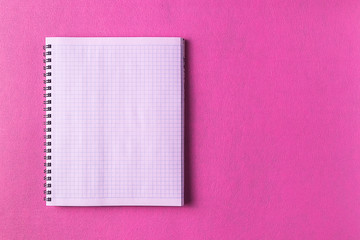 Minimalism style. White  sheet of notebook and  a pencil paper against  pink paper background; flat lay; copy space.