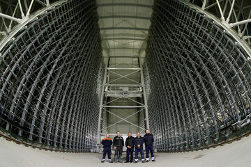 Employees pose between the steel frames of a high rise warehouse, currently under construction at metal distributor Debrunner Acifer AG in Birsfelden