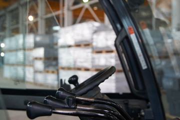 Cabin forklift truck with levers and steering wheel control in factory warehouse on background